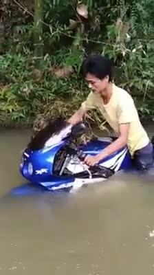 Người đàn ông tự tin mang chiếc mô tô đùa nghịch ở sông