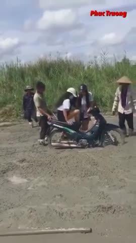 2 cô gái đi xe máy lao thẳng vào đường đang đổ bê tông, các bác công nhân hết sức giúp đỡ mới thoát được ra ngoài