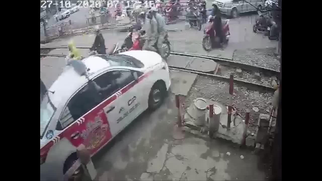 Taxi mắc kẹt trên đường ray tàu được nhân viên cùng người dân hỗ trợ giải cứu