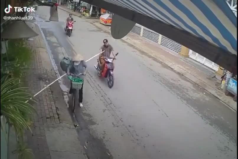 Người phụ nữ dùng 'gậy Như Ý' một chạm đẩy ngã người đàn ông đang đi xe máy